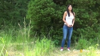 Brazen blonde female in denim pants Rebecca pees within the forest